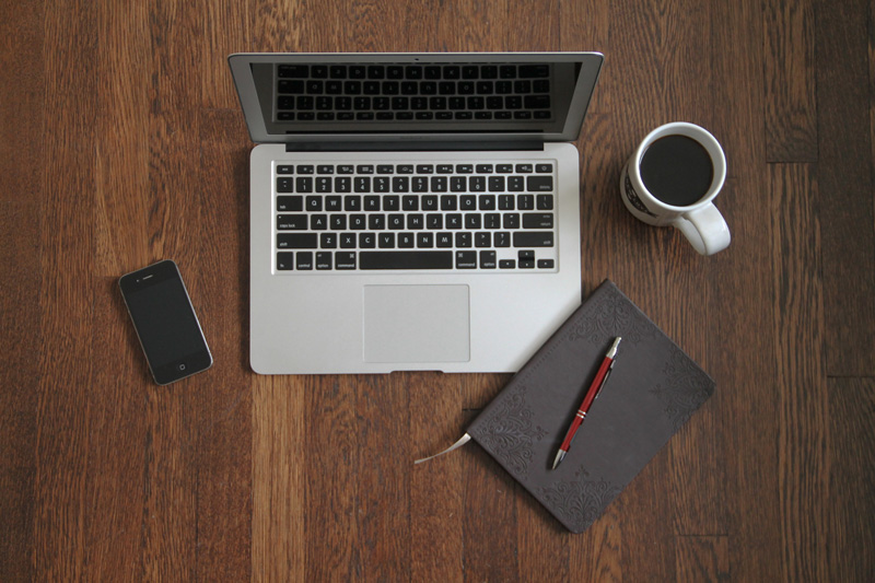 This is a photo of a laptop and a cup of coffee and a journal on a desk