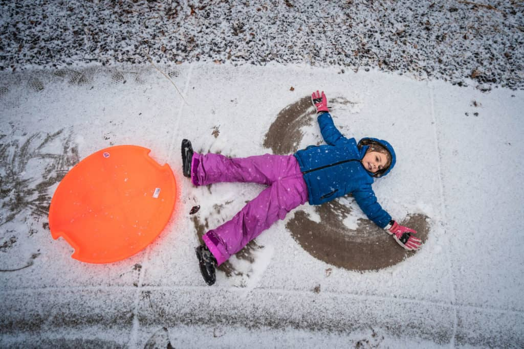 child playing in the snow over winter break as example of school marketing plans